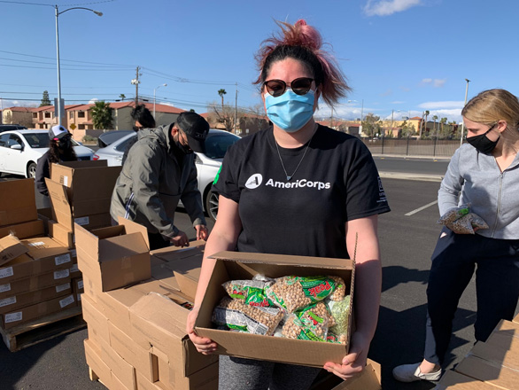 4-H AmeriCorps member holding a box of food to hand out.