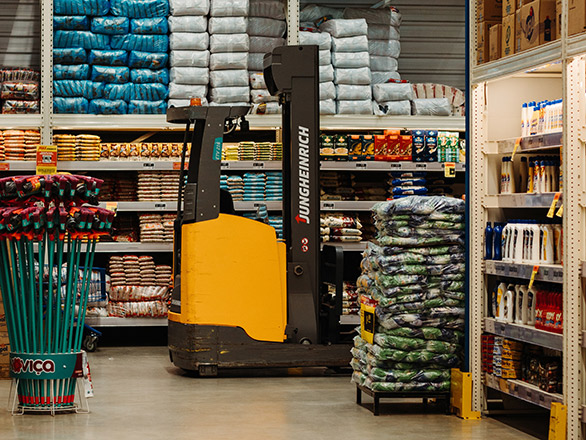 Warehouse full of stock items with forklift sitting in front