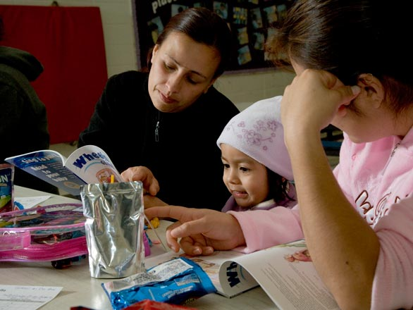 Two women read a book with a little girl at a Family Storyteller workshop
