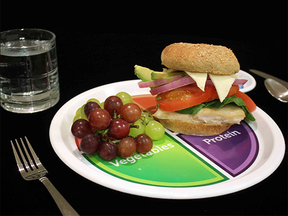 A healthy meal: chicken sandwich and grapes on a plate and a glass of water.